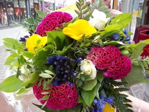 Bouquet of unusual flowers, bright pink, blue, yellow and white set off with green foliage