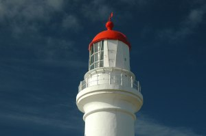 Photo of a white lighthouse with a red turret