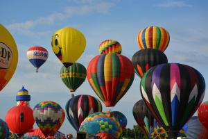 hot air balloons lifting into sky - bright yellow smiling air balloon rising highest
