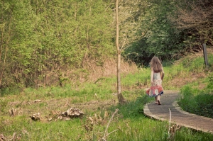 photo of a young girl walking down a winding path int he countryside