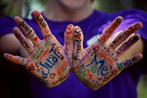 Photo of two hands graffittied with words of aceptance