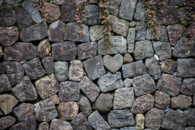 60507875 - heart shaped stone hidden in the rocky stone wall
