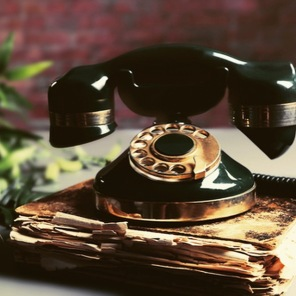 Old telephone with book on the table, close up