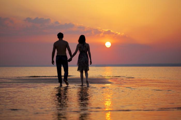 COUPLE WALKING BEACH AT SUNSET