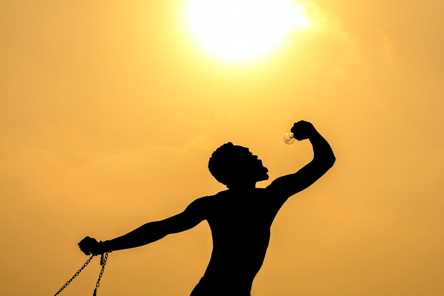unrecognizable man with bulb against sundown sky